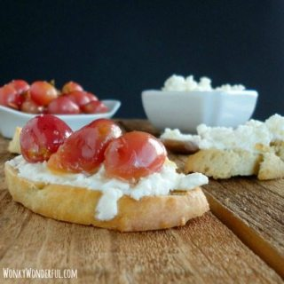 ricotta and roasted grape crostini on wooden board