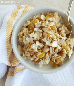 brown rice topped with golden raisins, coconut and almonds in white bowl