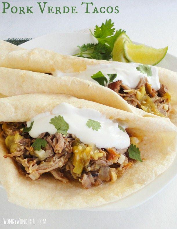 Pork Tacos with cilantro and sour cream served on white plate, photo text: pork verde tacos