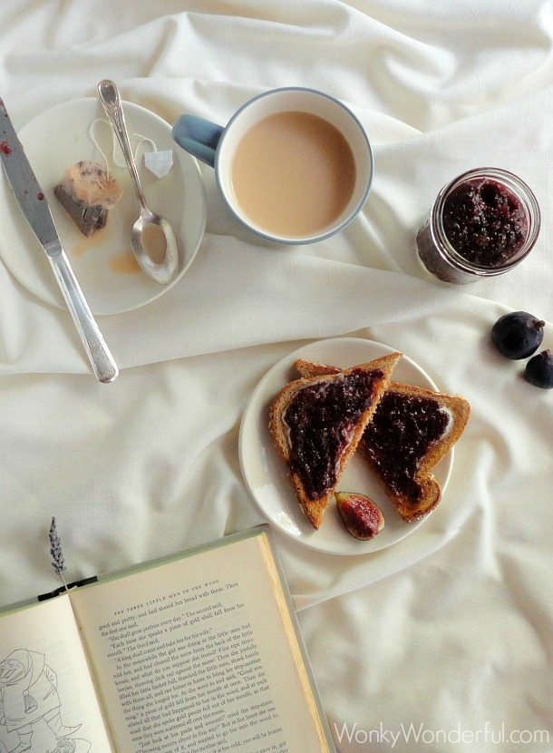 cup of tea, fig jam toast and book layer out on tablecloth
