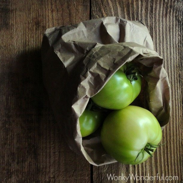 green tomatoes in brown paper bag