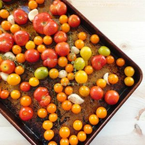 dark rimmed baking sheet with tomatoes, garlic and thyme
