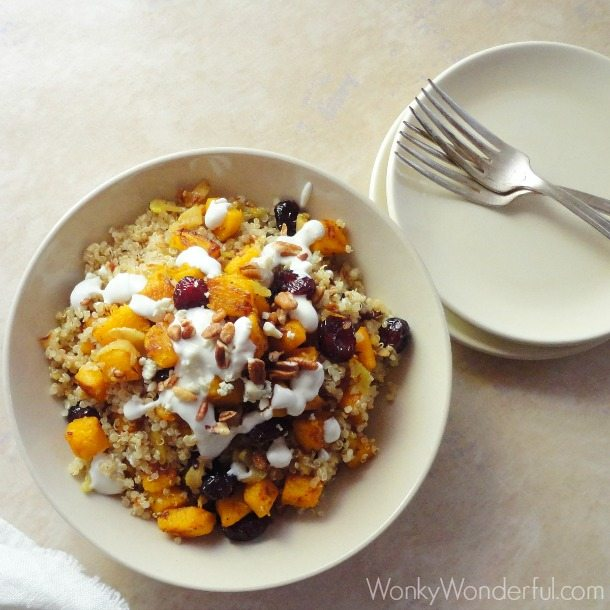 quinoa, pumpkin and cranberries in beige bowl next to plates and forks