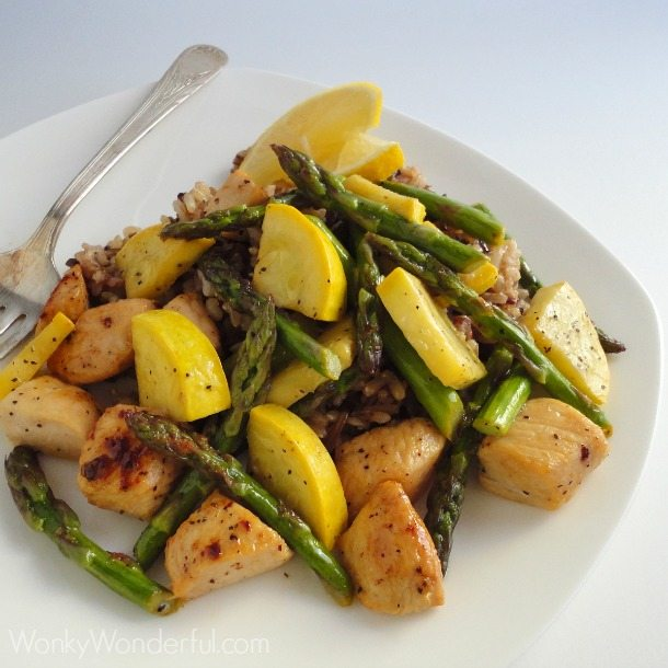 chicken, squash, asparagus and rice served on white plate with fork