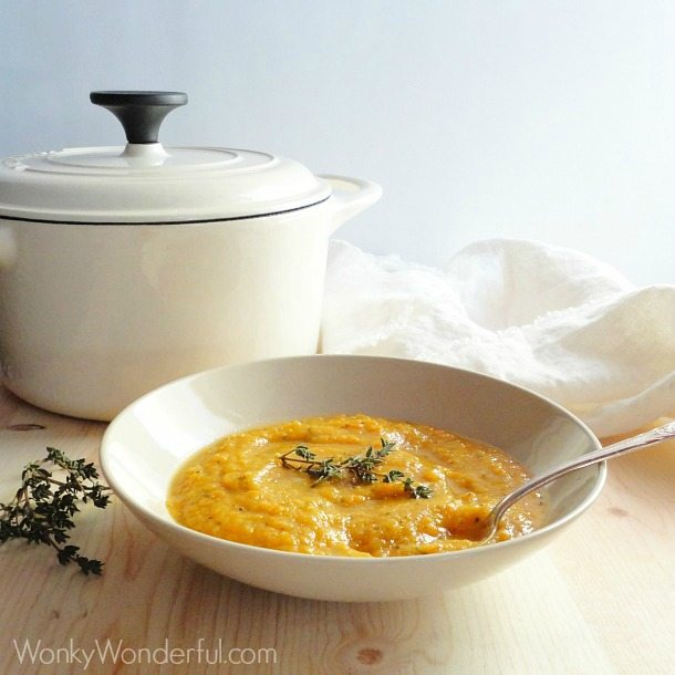 pureed orange colored soup in beige bowl next to white enamel pot