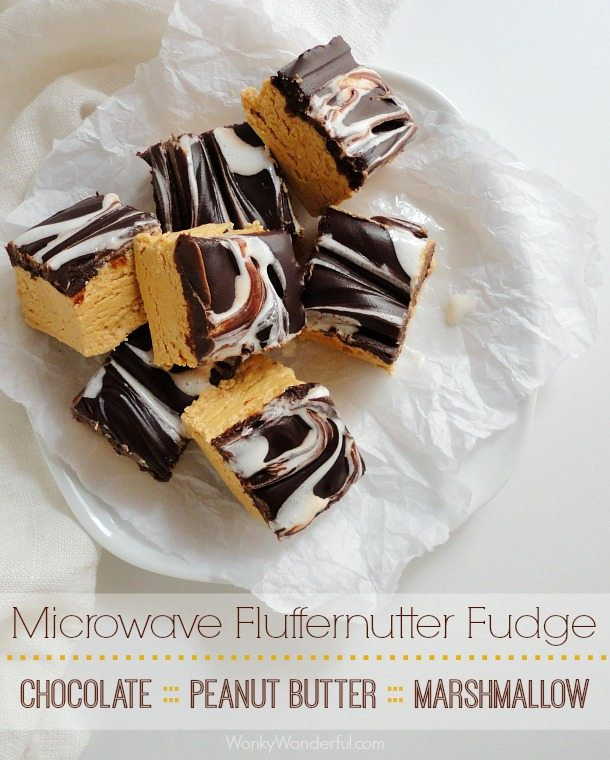 brown and white swirl top tan fudge squares on white dish with wax paper