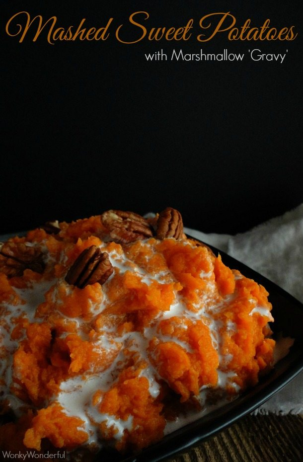 mashed sweet potatoes topped with marshmallow and pecans in black dish