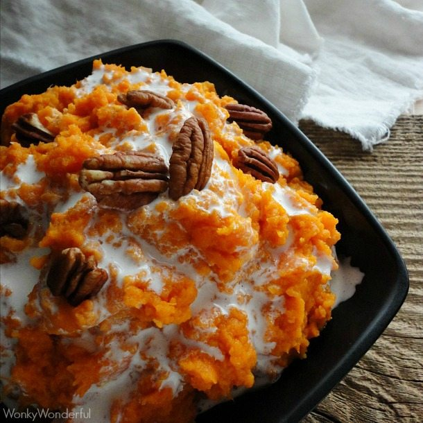 mashed sweet potatoes topped with marshmallow and pecans in black bowl