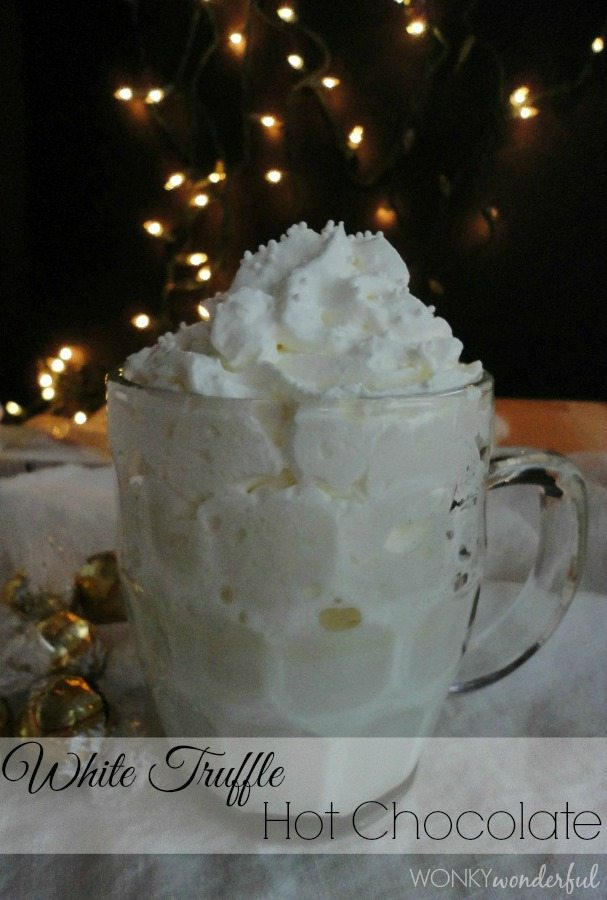 clear glass mug filled with white beverage and whipped cream - photo text: white truffle hot chocolate