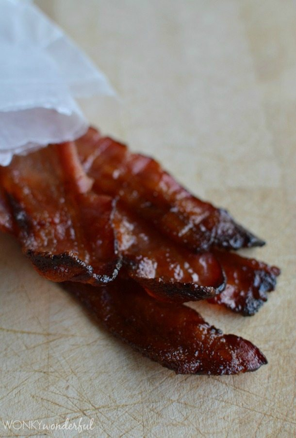cooked glazed bacon strips on wood cutting board