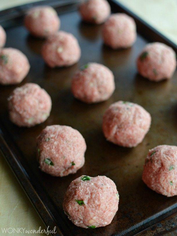 raw meatballs on dark rimmed baking sheet