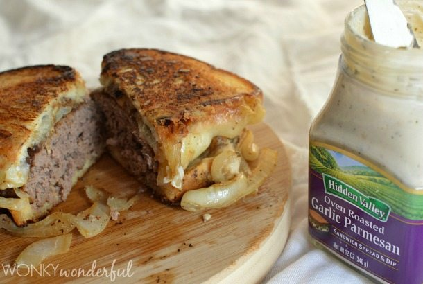 cooked patty melt cut in half next to jar of garlic parmesan spread