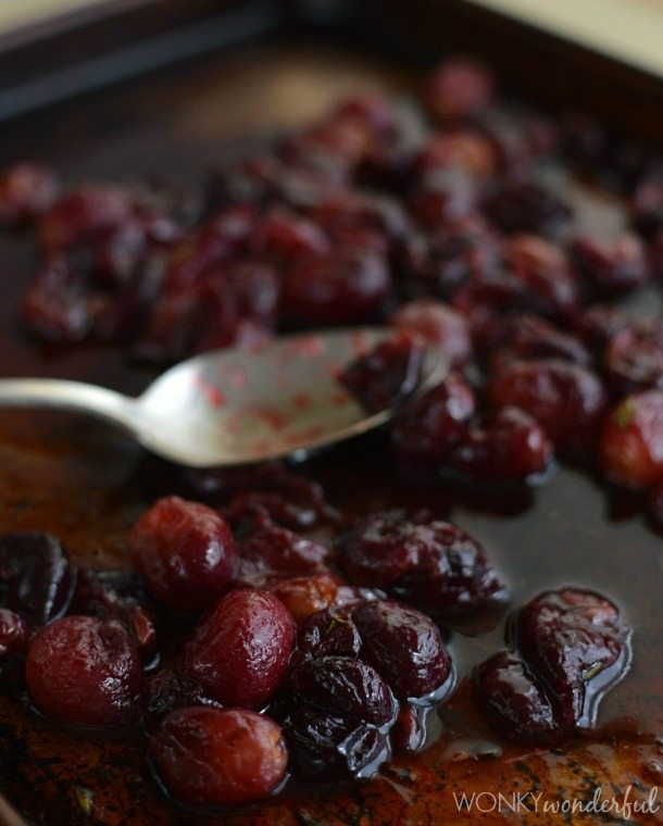 roasted grapes on rimmed baking sheet with spoon