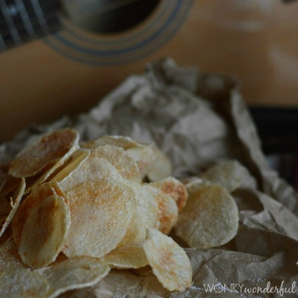 thinly sliced cooked potato chips on brown paper