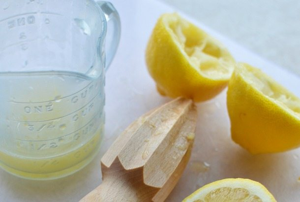 lemon halves next to glass measuring cup with juice inside