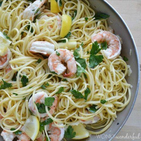 thin pasta, pink shrimp, lemon and parsley in pan