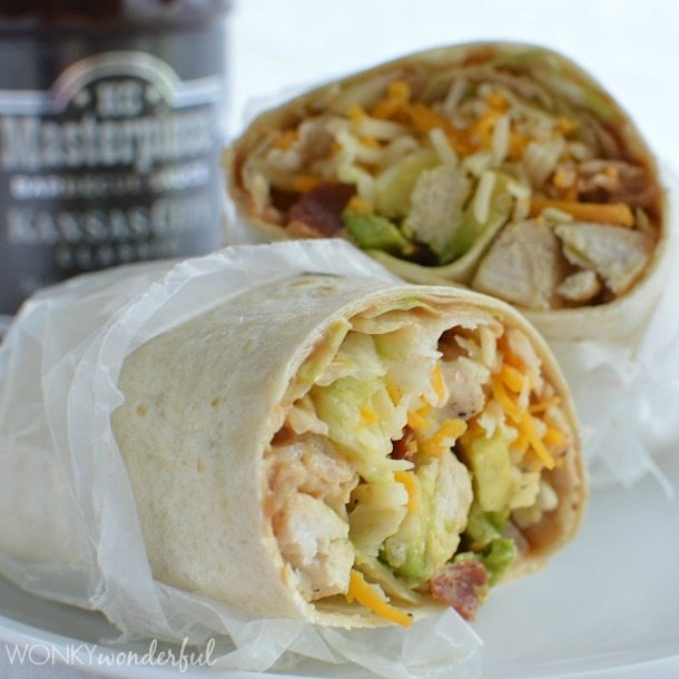 Chicken wrap cut in half with cheese, avocado and chicken showing inside