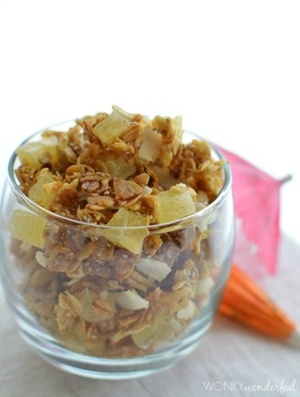 chunky granola in clear glass next to mini cocktail umbrellas