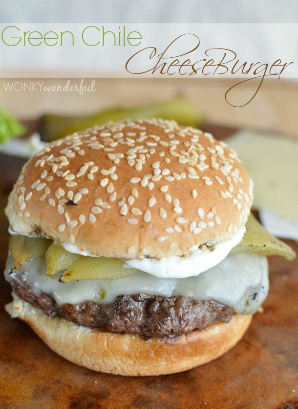 sesame seed bun filled with cooked burger, melted cheese and a large green Chile - photo text: green Chile cheeseburger