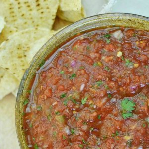 deep red salsa in brown bowl next to tortilla chips