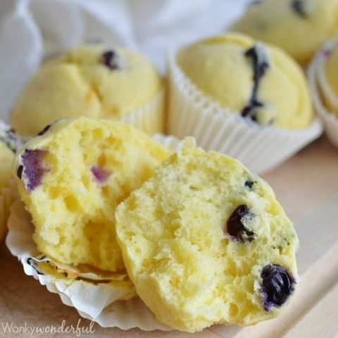 yellow muffin with blueberries broken in half
