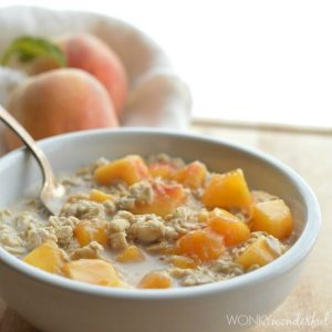 oatmeal and peaches in white bowl with spoon