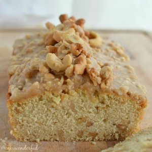 light tan quick bread topped with glaze and cashews