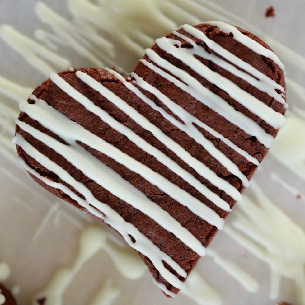 This Red Velvet Brownie Recipe makes the perfect Valentine's Day Dessert! Chocolate Fudge Brownies with that red velvet color. Cut into heart shapes then drizzled with white chocolate!