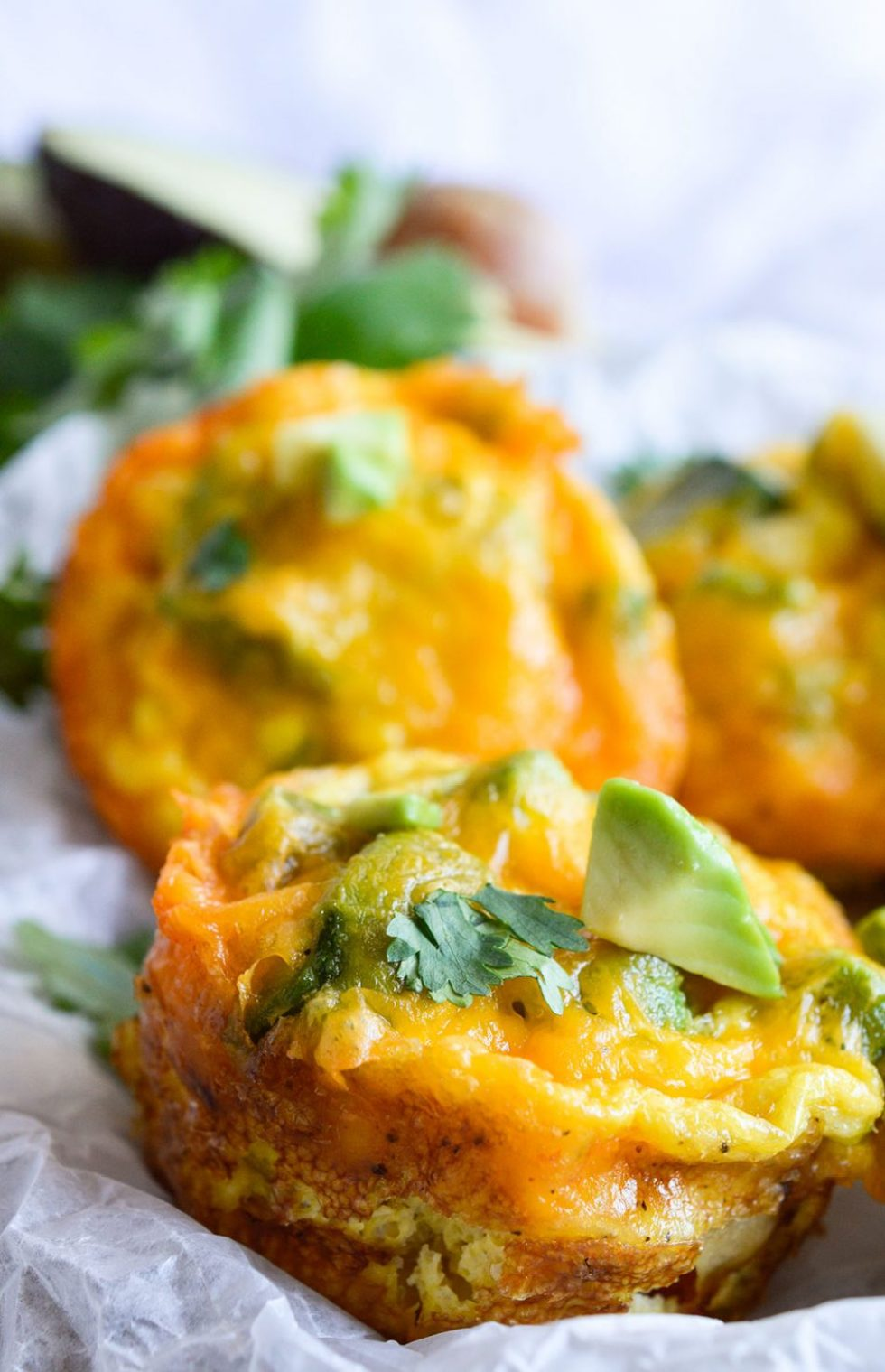 These Cheesy Avocado Egg Muffins are great for feeding a hungry breakfast or brunch crowd! All your favorite breakfast ingredients in one bite sized vegetarian egg muffin.