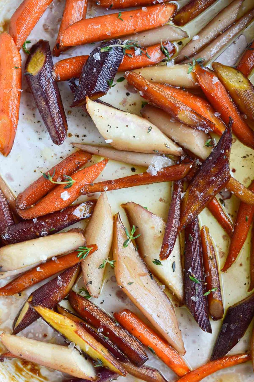 Enjoy your favorite holiday side dish without the guilt. These Healthy Candied Carrots are roasted with olive oil, maple syrup and thyme. Sweet and salty roasted carrots will be a new family favorite! Vegan, Vegetarian, Paleo #paleorecipes #veganrecipes