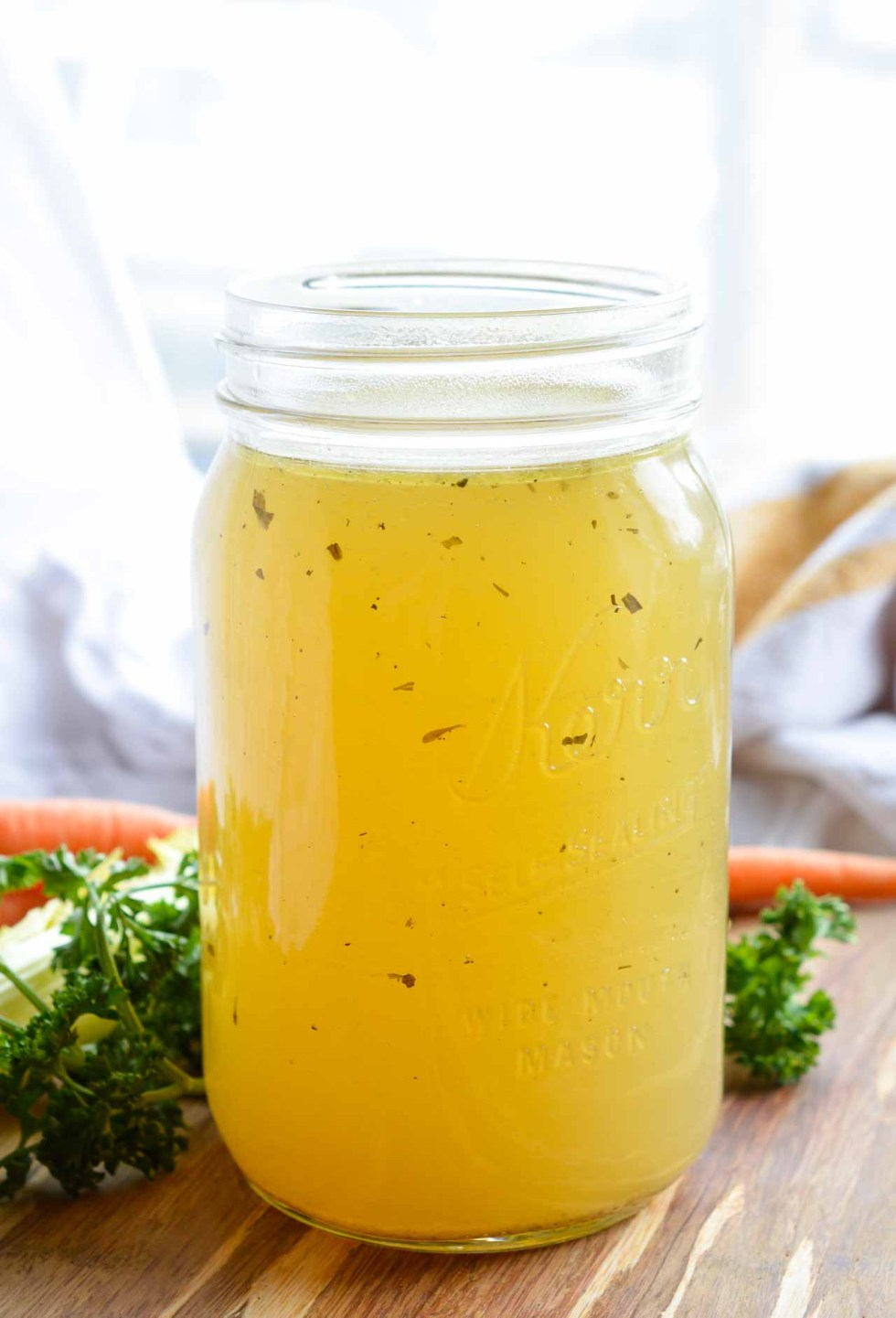 This Homemade Chicken Stock Recipe is so flavorful and easy to make. Just toss the ingredients into your slow cooker and forget about it. 12 hours later you have the most amazing chicken broth just waiting to be used! Whole30, Paleo #paleorecipes #whole30recipes