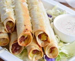 If you have leftover corned beef after Saint Patrick's Day, make this Reuben Stuffed Baked Taquitos Recipe! These homemade taquitos are filled with corned beef, sauer kraut and swiss cheese. Dip them in thousand island dressing for the ultimate meal or snack!