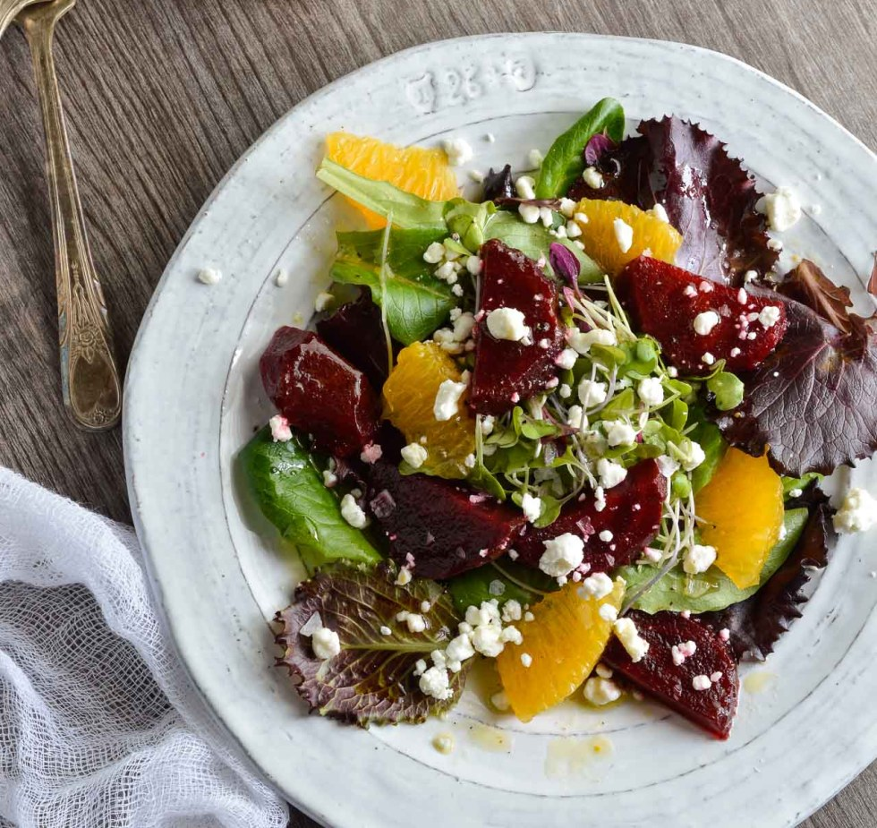 bett salad with bright maroon beets, orange segments, greens and goat cheese crumbles