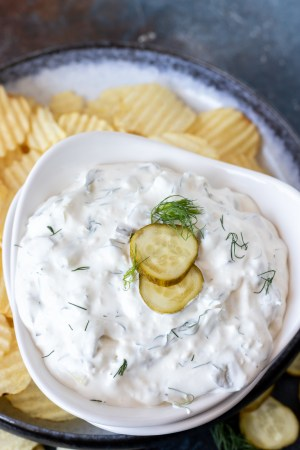 creamy dip topped with pickle slices and fresh dill