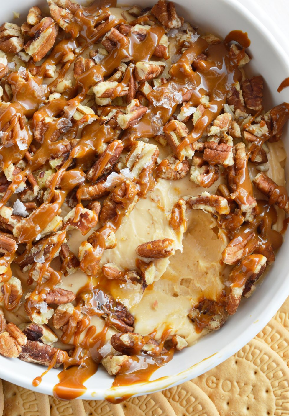 cheesecake dip topped with drizzled caramel and pecans