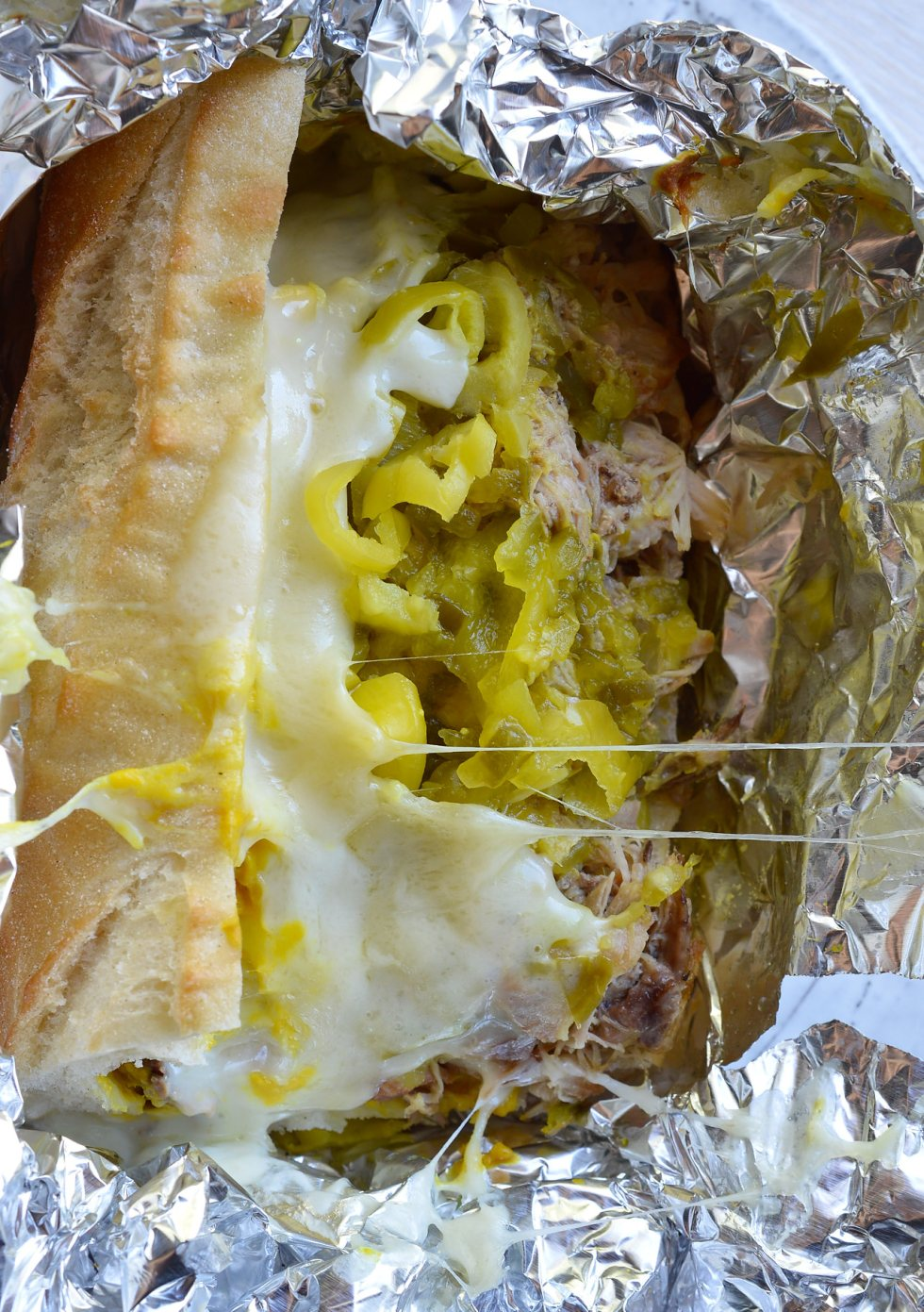 If you are tired of the same old barbecue pork sandwiches give these Slow Cooker Pulled Pork Cuban Sandwiches a try! This easy dinner recipe is inspired by Cuban Sandwiches. Start with Coca-Cola slow cooker pulled pork then add cheese, peperoncinis, pickles, mustard and bread. These oven baked sandwiches are perfect for feeding a crowd!