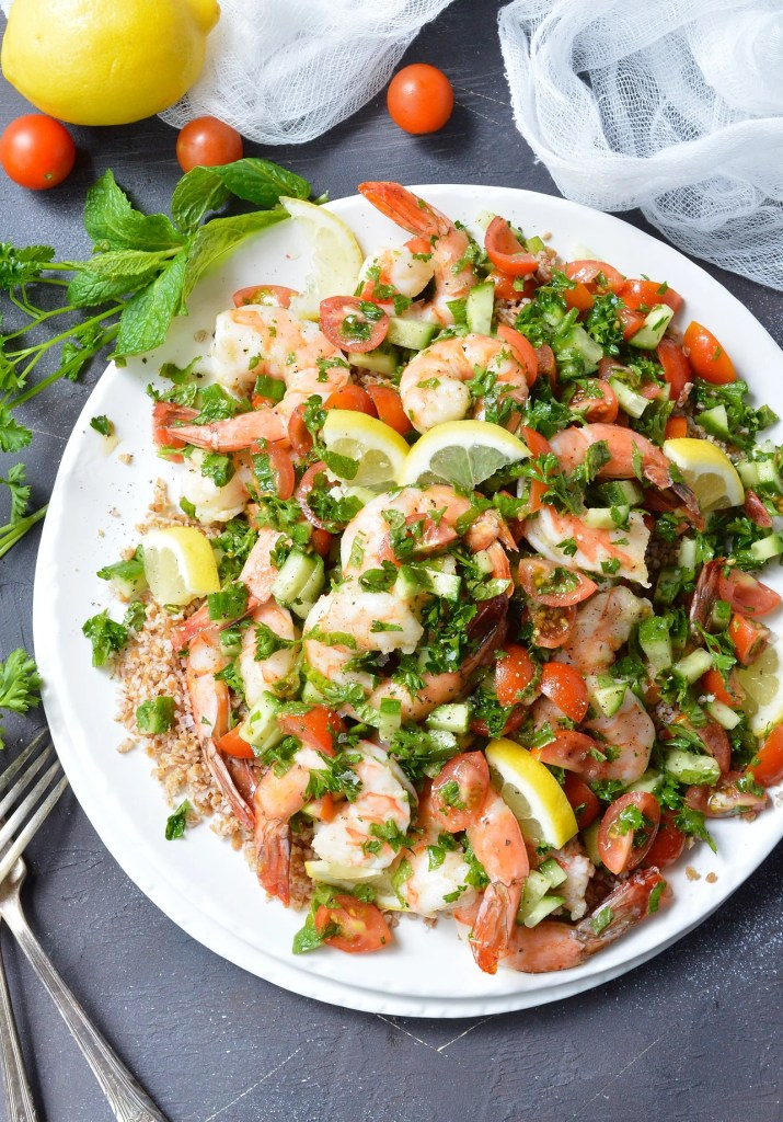 shrimp salad with mint and parsley served on white plate