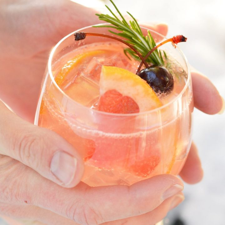 two hands holding glass filled with fizzy cocktail, grapefruit and cherries