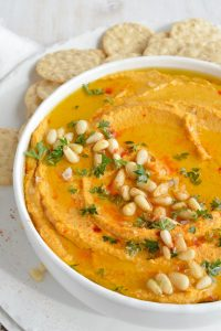 pumpkin hummus in white bowl with crackers on the side