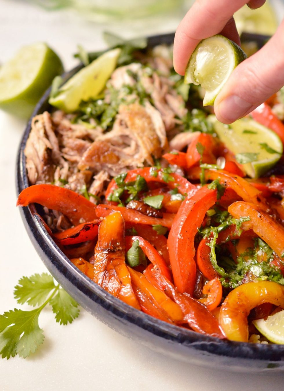 squeezing lime juice over pork fajita bowl