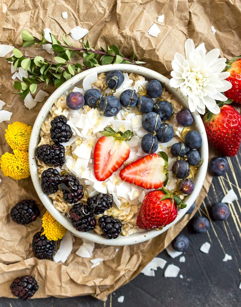 a white bowl filled with oatmeal, berries, coconut chips with flowers and berries on the side