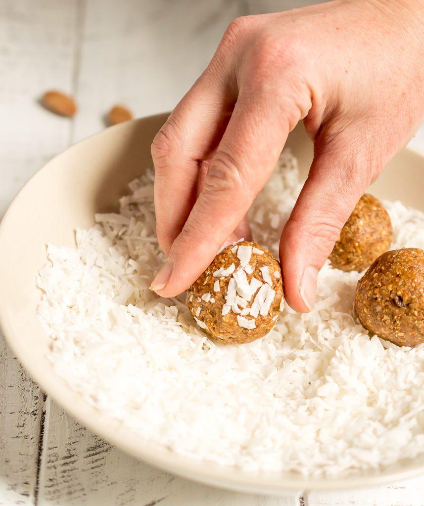 hand rolling energy balls in bowl full of shredded coconut