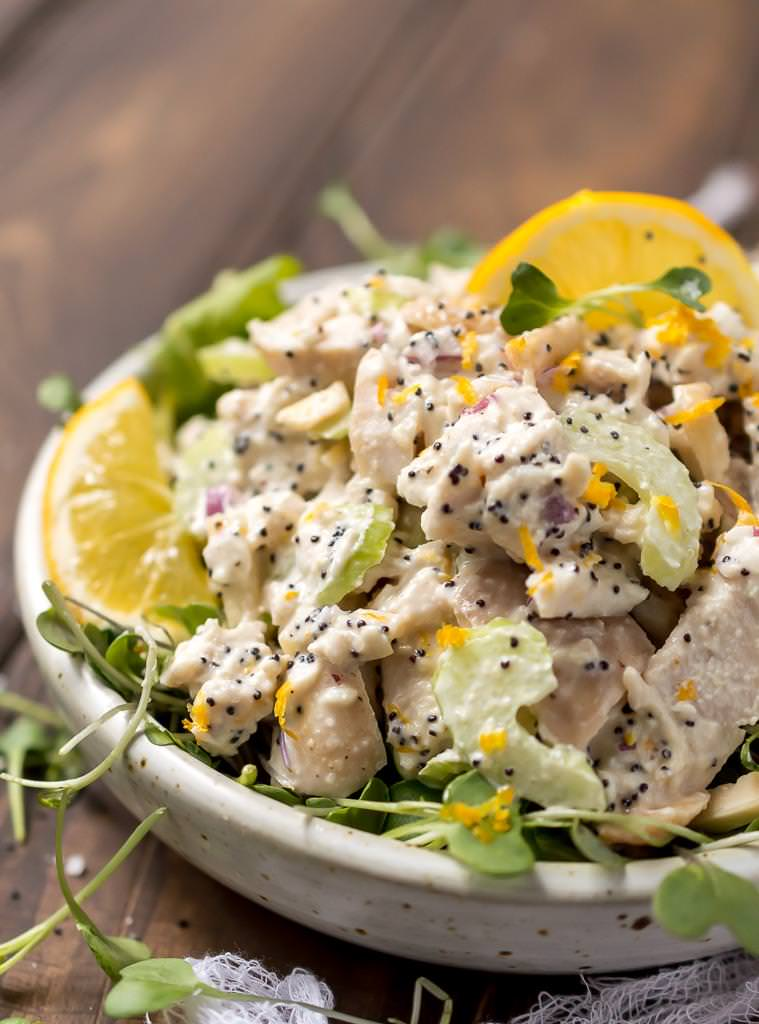 side view close up of lemon chicken salad with black poppy seeds and bright yellow lemon slices
