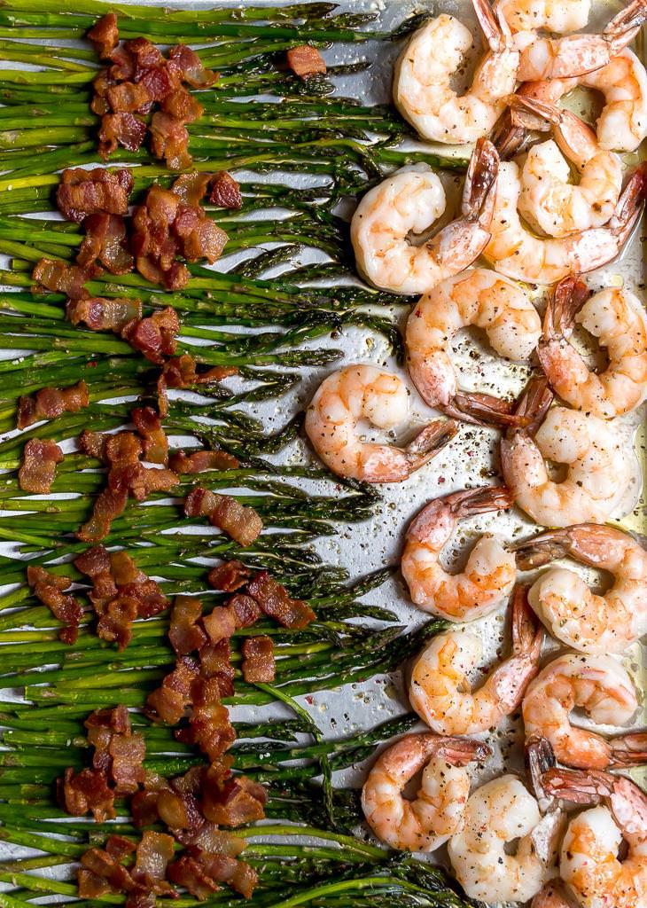 asparagus, bacon and shrimp arranged on a sheet pan