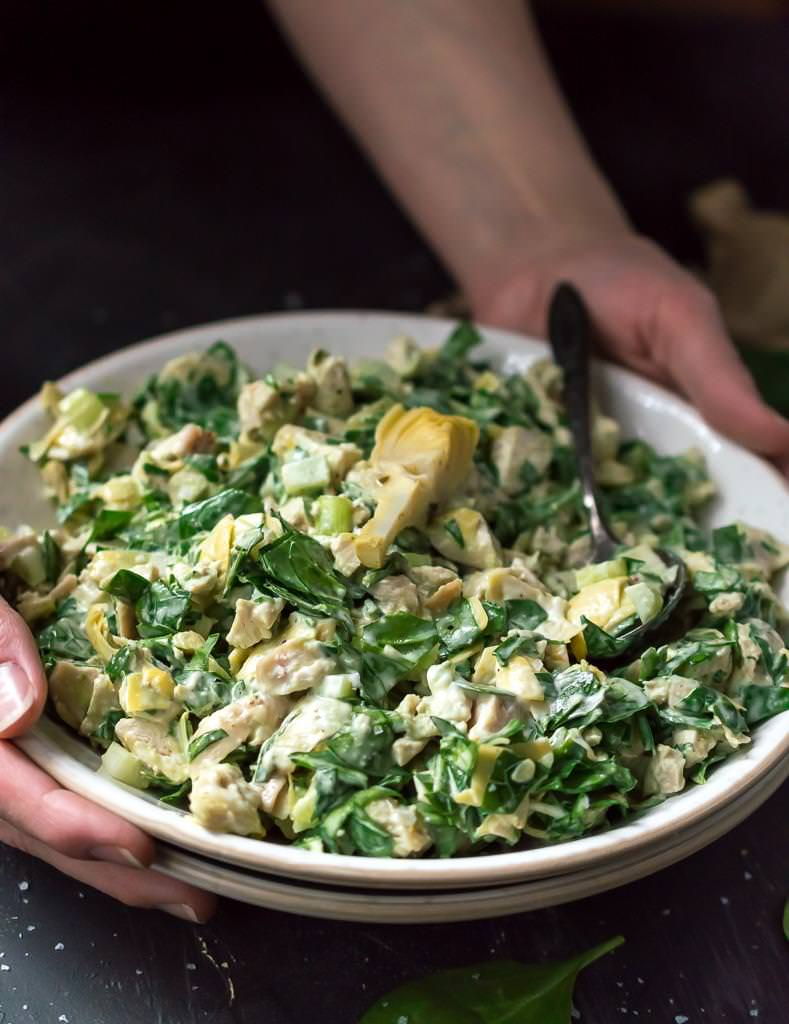 two hands carrying white bowl filled with spinach artichoke chicken salad for serving