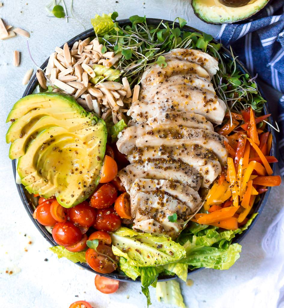 overhead photo of large round bowl filled with salad, veggies, chicken and honey mustard dressing