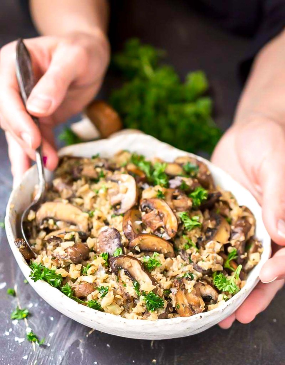 hands holding bowl of cauliflower rice with mushrooms