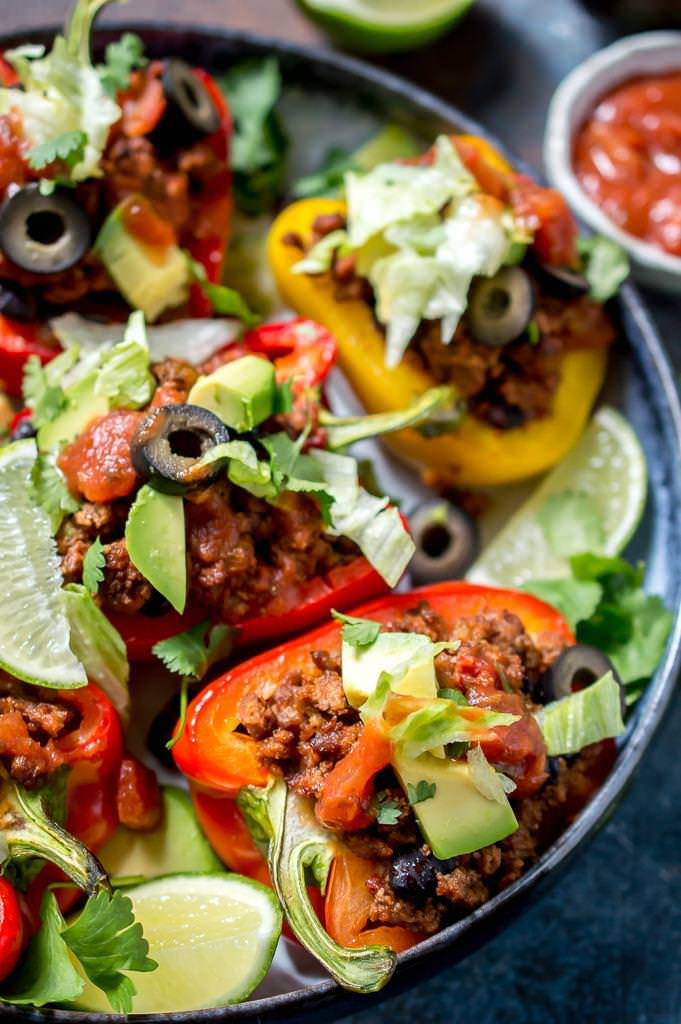 close up of stuffed peppers topped with lettuce, avocado, olives and cilantro.