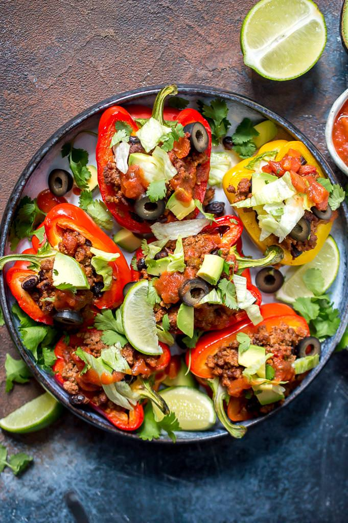 close up photo of taco stuffed peppers in round dish with blue rim. Peppers topped with lettuce, avocado, black olives, cilantro and salsa.