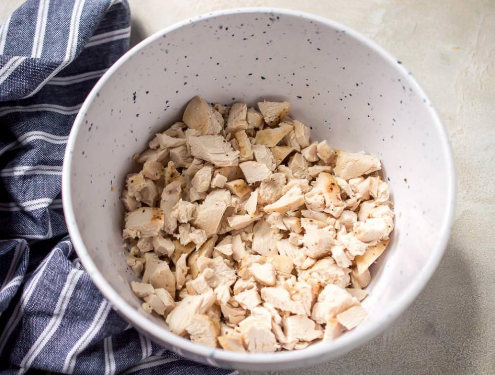 baked chicken breast that is chopped and in a white bowl with blue flecks